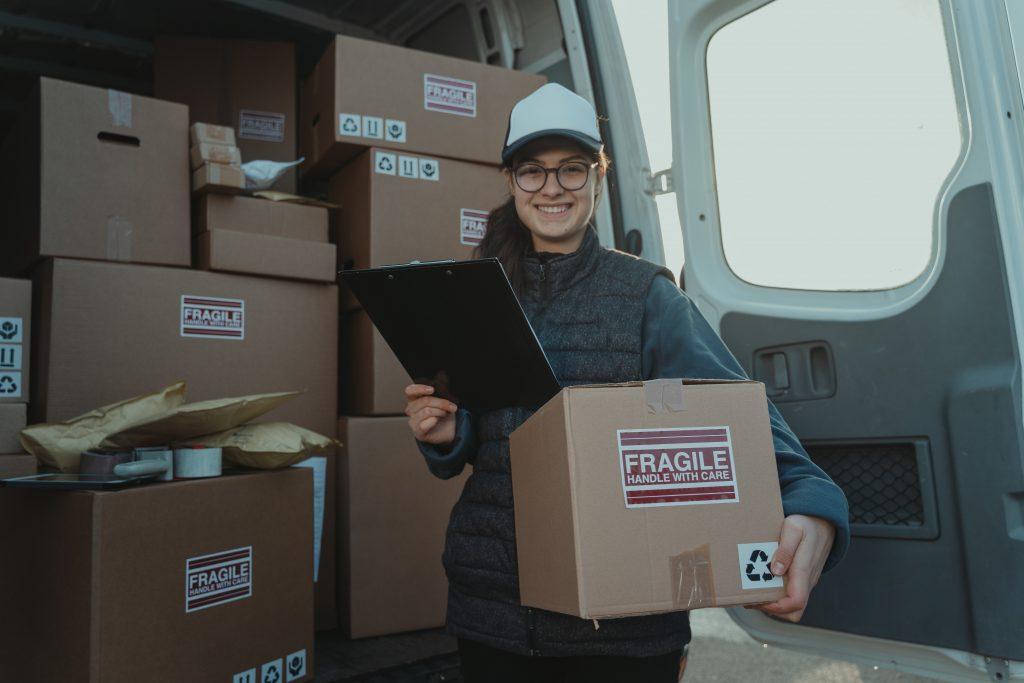 a happy route delivery driver holding a package and a clipboard